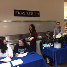 Students at a table in front of the tray return sign in the cafeteria.