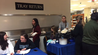 Students at a table in front of the food tray return sign in the cafeteria.