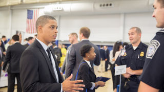 A student networking with an employer at the Career Fair.