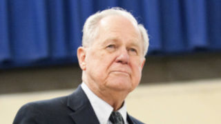 Photo of Jim McGlone, a pale man who is about 70 years old, has white hair, and is wearing a navy suit.