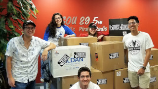 Five students are posed around boxes inside the WSOU 89.5 FM station containing items for the clothing drive.