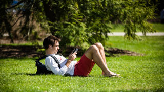 Student on the green using phone.