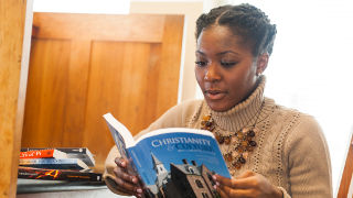 Student reading Christianity and Culture in Dialogue book in the library.