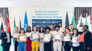 Diplomacy students standing in front of flags at the PPIA Public Service Weekend. The students are each holding certificates of completion of the program.