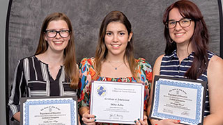 A photo of Catherine Way, Irina Acha and Bethany Wood holding their certificates.