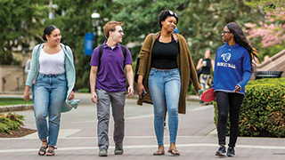 A group of undergraduate students walking on campus.
