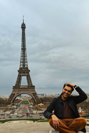 Student sitting in front of the Eiffel Tower