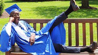 Martin Tettey sitting on a bench while wearing graduation attire. x320