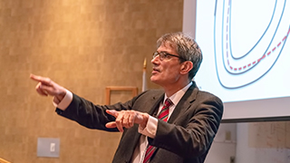 Sir Steven Cowley presenting a lecture.