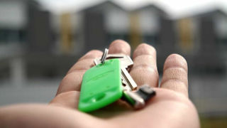 A person holding house keys in the palm of their hand.