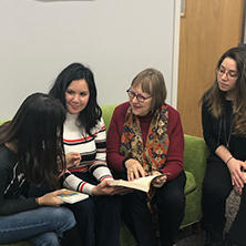 Students sitting on a couch with Dr. Catherine Tinker