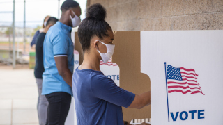 Young people, wearing masks, and voting in the election.