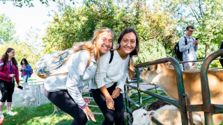 Two students standing next to goat at the Welcome Week petting zoo.