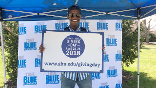 Student holding up a Giving Day sign under the TrueBlue tent on the University Green.