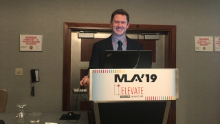 Kyle Downey smiling and standing behind a podium at the 2019 MLA National Conference in a conference room.