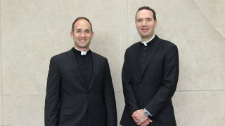 Photo of Fr. Laracy and Fr. Platania in front of the mural in McNulty Hall.