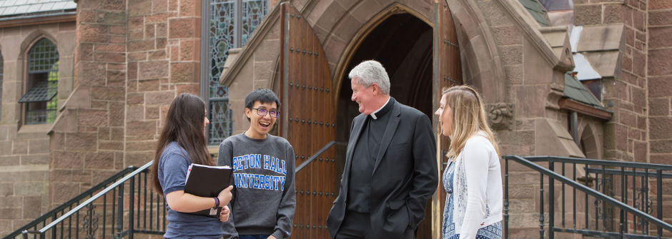 A priest laughing with students outside the Chapel of Immaculate Conception.